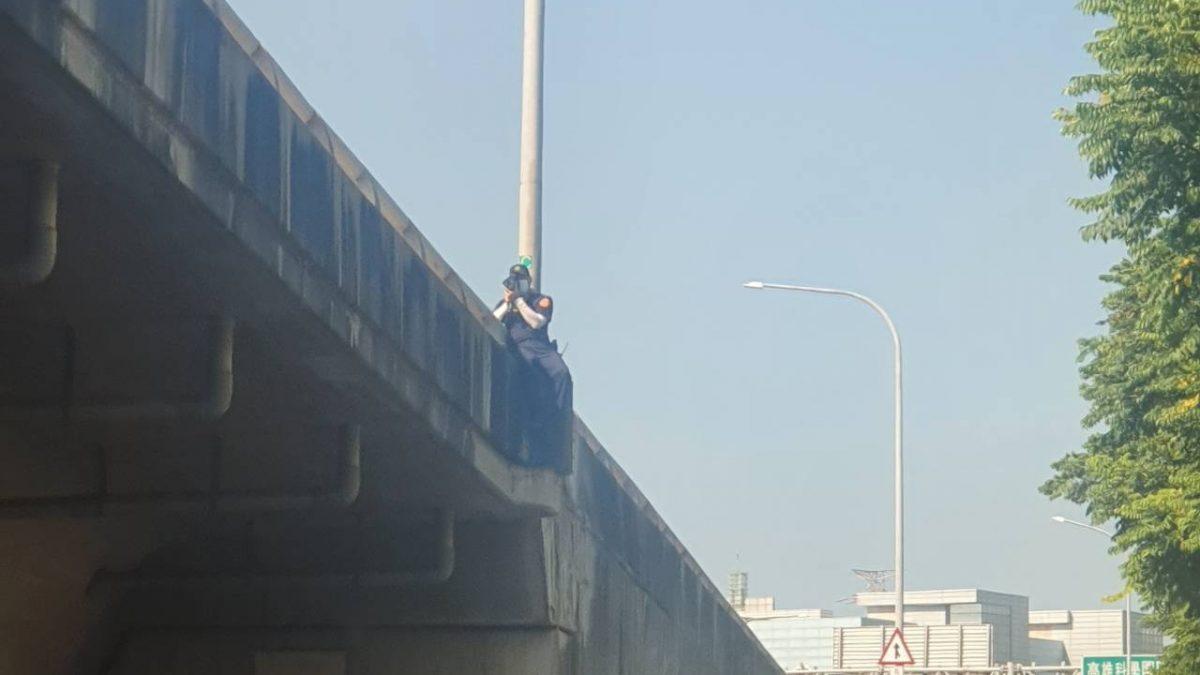 驚!國道警察取締違規 竟爬出護欄外?